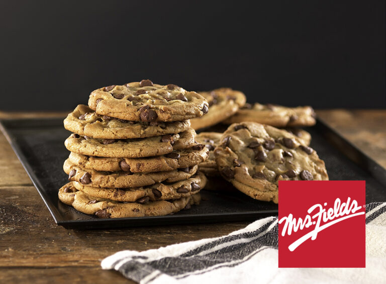 chocolate chip cookies stacked on top of each other on black pan with white towel all on wooden table. Has Mrs. Fields logo.